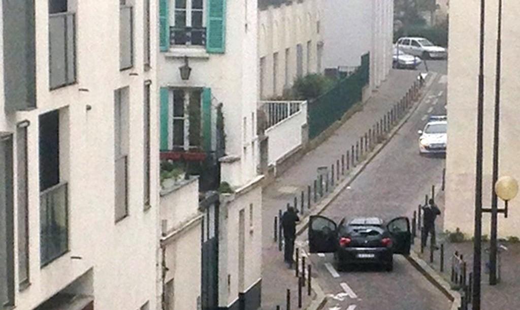 HENRETTET TOLV: Væpnede terrorister står overfor politiet utenfor inngangen til det franske satiremagasinet Charlie Hebdo onsdag.