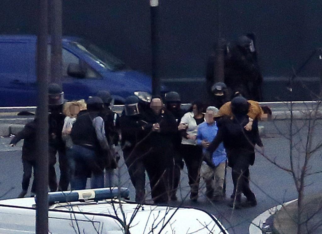 Spesialstyrker fra det franske politiet frakter gisler ut fra kosher-butikken i Paris, der en gisseltaker holdt fem personer fredag.