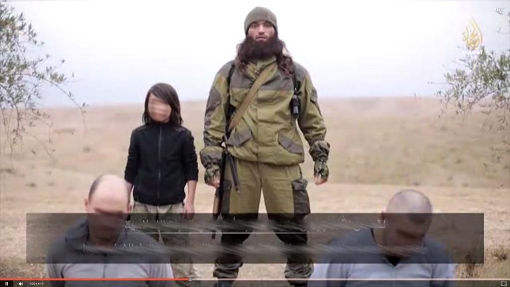 GUTTEN: Videoen viser gutten mens han står ved siden av IS-soldaten som siterer Koranen. Foran ser du de to mennene som blir skutt.