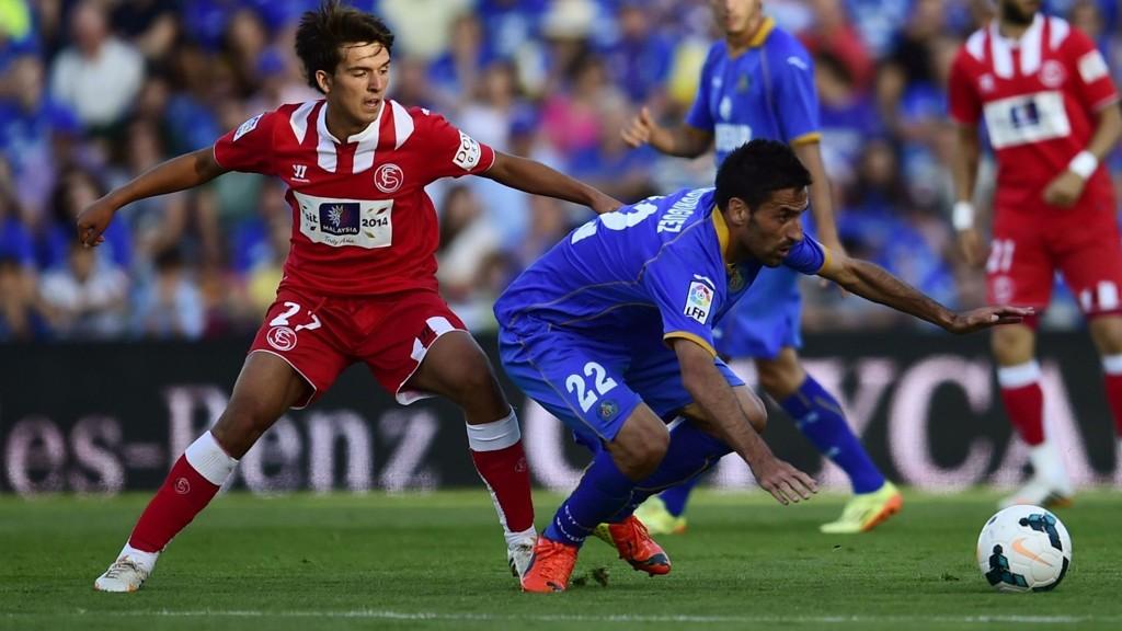 Getafes midtbanespiller Juan Antonio Rodriguez i duell med en Sevilla-spiller.