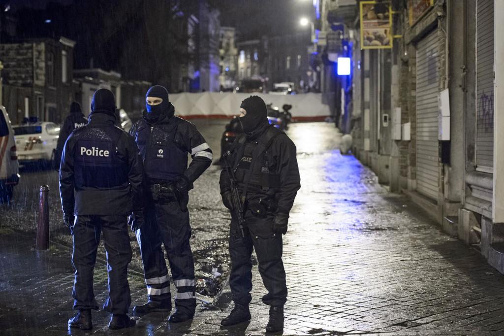 Belgiske politistyrker stengte av gaten mens de undersøkte leiligheten som ble stormet i antiterroraksjonen.