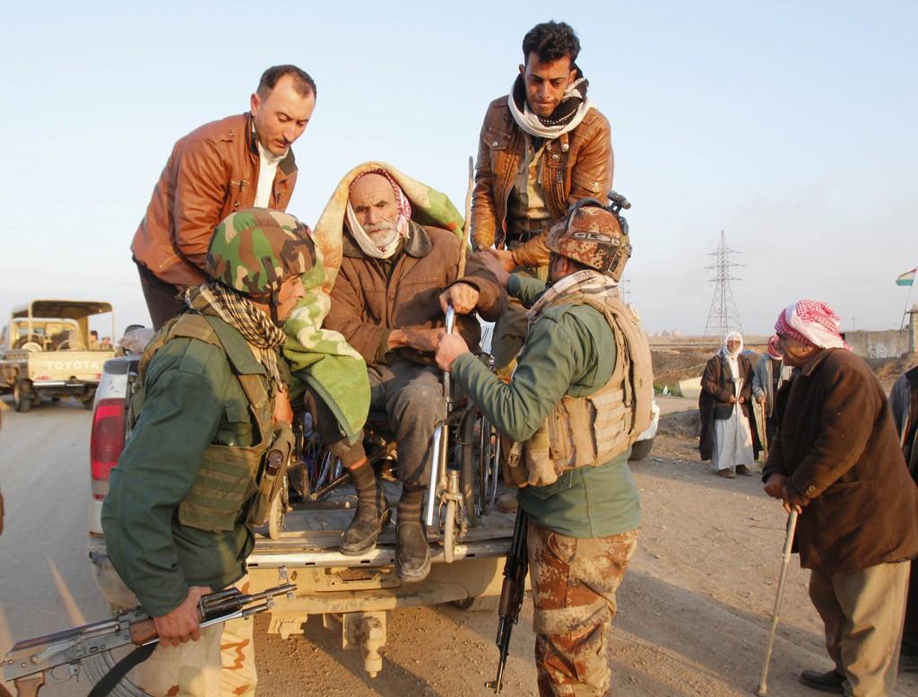 FÅR HJELP: Kurdiske sikkerhetsstyrker hjelper en av yezidiene som ble sluppet fri av IS utenfor Kirkuk.