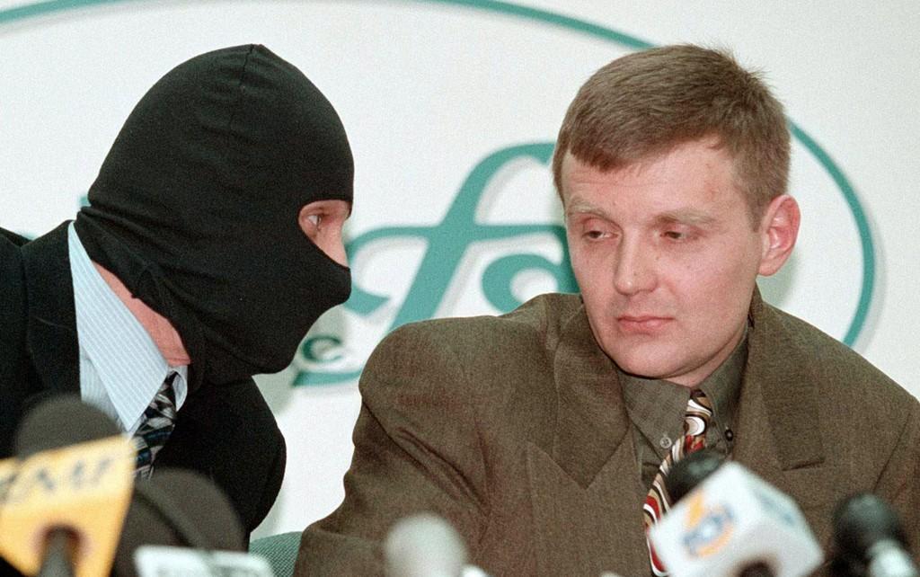 Aleksandr Litvinenko (til høyre) avbildet i 1998 under en pressekonferanse, da han ennå var oberst i den russiske sikkerhetstjenesten FSB, som er arvtakeren til KGB. Ved siden av ham sitter en FSB-kollega som er maskert for å skjule sin identitet.