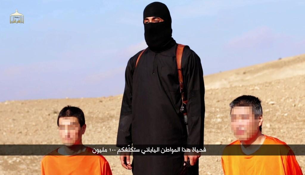 Skjermbildet over er tatt fra en video angivelig produsert av IS 20.01.15. De to japanske gislene Kenji Goto (til venstre) og Haruna Yukawa omkranser en IS-terrorist. Yukawable trolig drept i forrige uke.