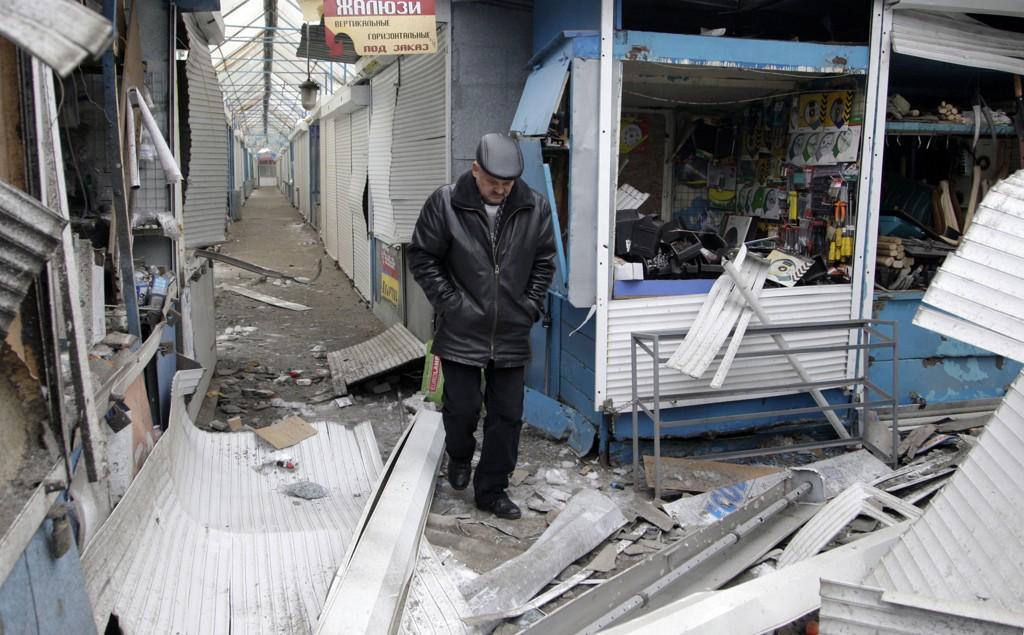 En mann går forbi butikker i Donetsk som har blitt ødelagt under kamphandlinger mellom ukrainske styrker og prorussiske separatister. )