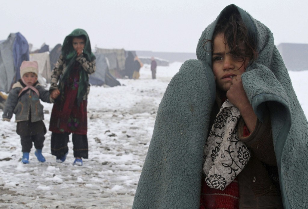Barn på flukt internt i Afghanistan avbildet ved en flyktningleir i den afghanske byen Heart. Barna står utenfor teltet sitt midt i vinterkulden. Forholdene for barnefamilier i Afghanistan blir stadig verre, ifølge Redd Barna. Likevel sendte Norge ut rekordmange asylbarn til det krigsherjede landet i fjor. Redd Barna sier også at noen barnefamilier selger barna sine for å overleve økonomisk (Illustrasjonsbilde).
