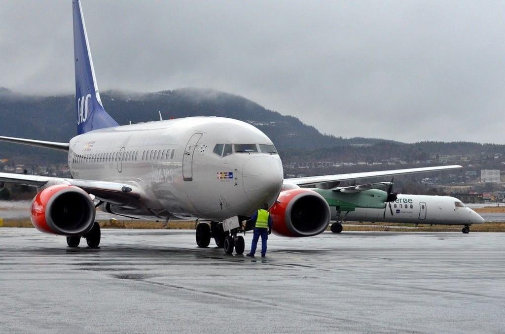 Illustrasjon: Et fly fra SAS på Trondheim Lufthavn Værnes. I bakgrunnen et Widerøe-fly.