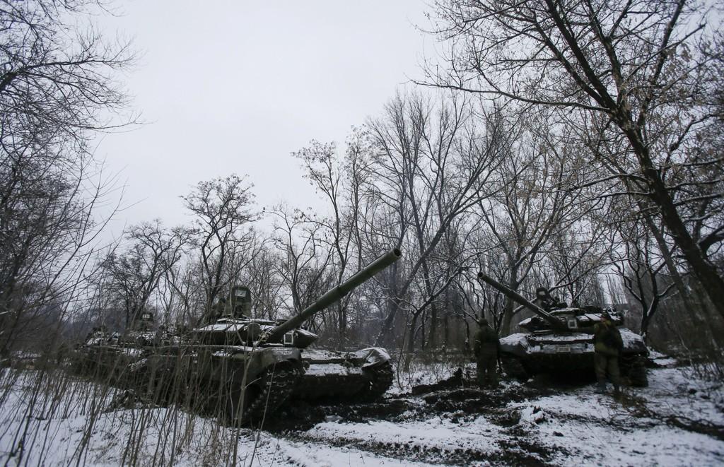 Pro-russiske separatister står ved stridsvogner i Horlivka i Øst-Ukraina 10. februar. Det er usikkert om stridsvognene i dette bildet har sammenheng med påstandene som framkommer i saken under.