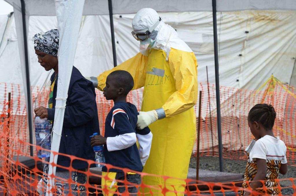 Den norske innsatsen mot Ebola har så langt i 2015 kostet 26 millioner kroner. Bildet: En helsearbeider fra Leger Uten Grenser følger en mor og hennes barn inn på et høyrisiko ebolasenter i Liberia.