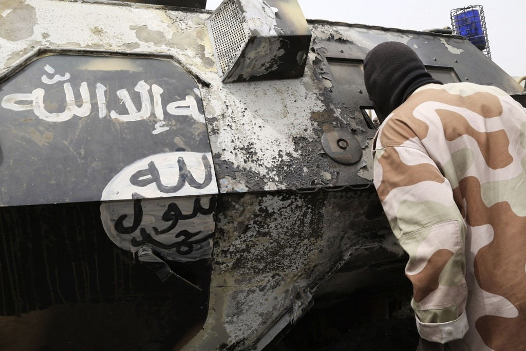 En soldat i Tsjad undersøker et pansret kjøretøy som skal ha blitt brukt av Boko Haram.
