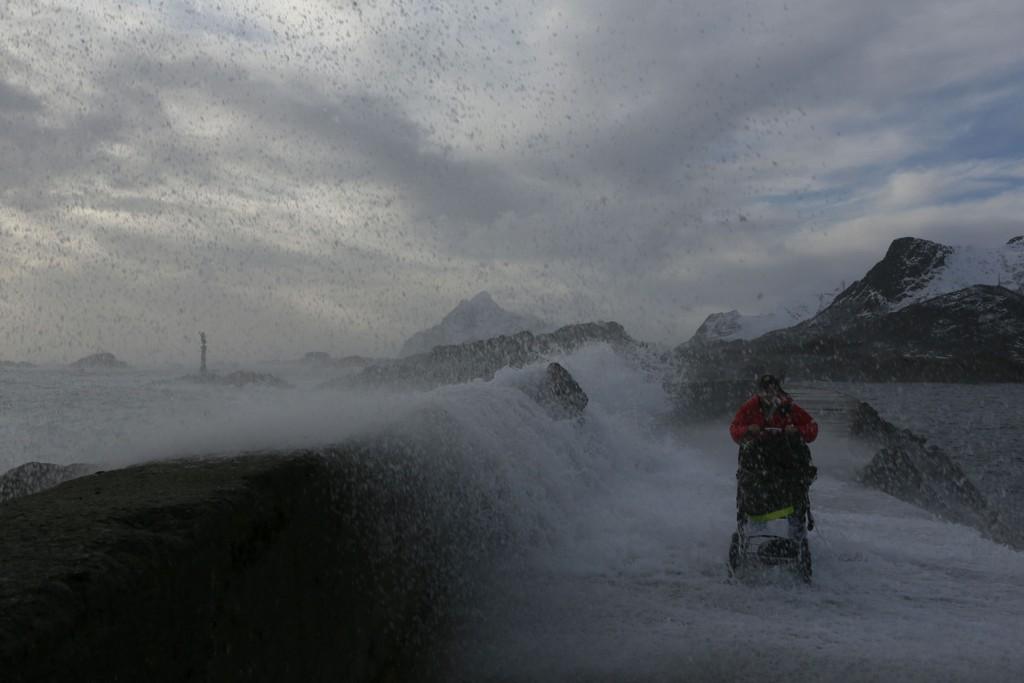 Her blir kvinnen med barnevogn nesten tatt av bølgene. En mann klamrer seg fast til muren.