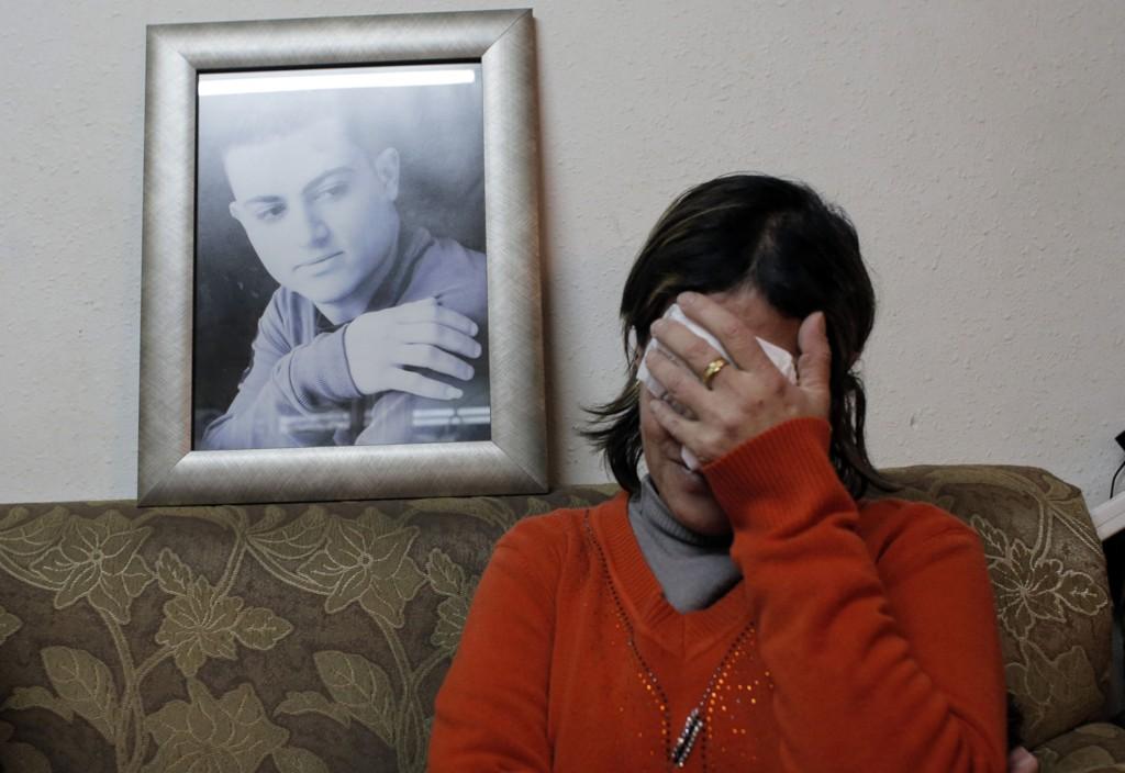 Moren til israelsk-araberen Mohammed Said Ismail Musallam sammen med et bilde av sønnen. Ekstremistgruppa Den islamske staten (IS) la tirsdag ut en video som angivelig viser Musallam bli drept av en gutt i tolvårsalderen.