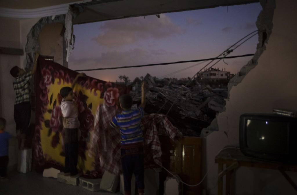 Barna i Harara-familien i Gaza henger opp tepper for å skjule ruinene utenfor soverommet sitt. Familien har flyttet tilbake i leiligheten siden de ikke har noe annet sted å bo. Nabolaget deres ble svært ødelagt av krigen i sommer. Totalt ble over 100.000 hjem ødelagt eller skadet.
