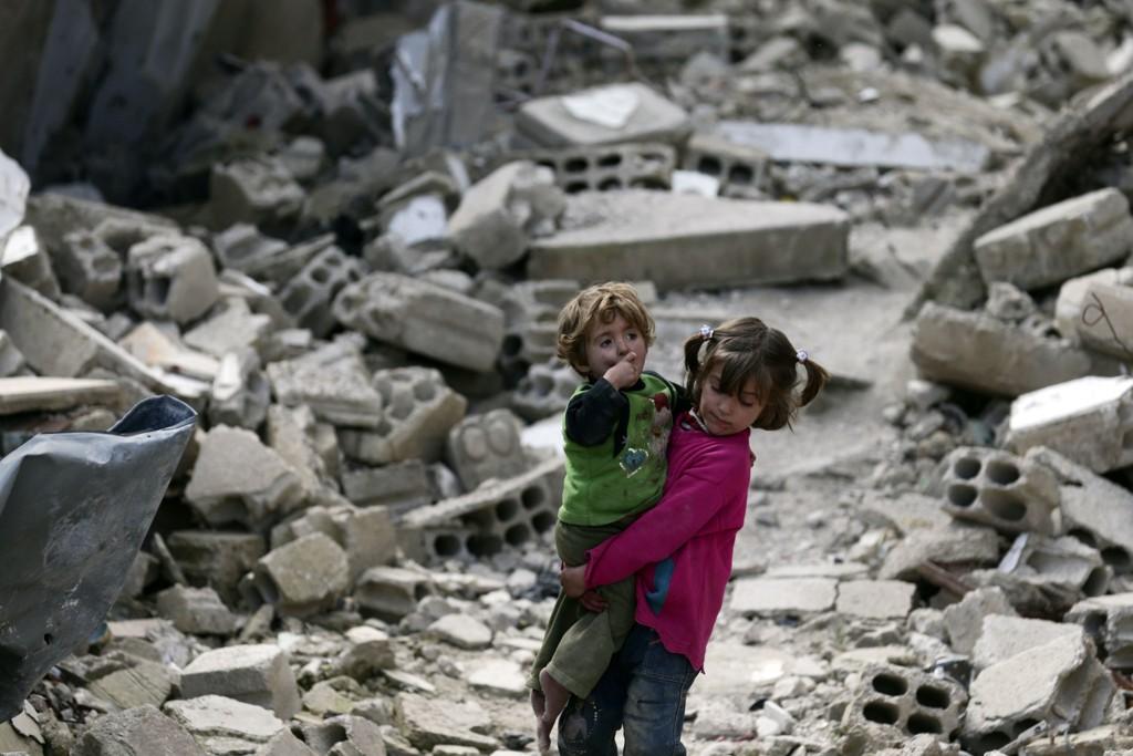 ALARMERENDE: Israa bærer sin søster, Boutol, gjennom ødelagt bebyggelse i Damaskus.