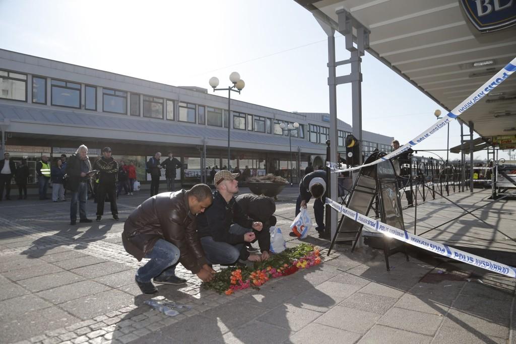 DREPT: To personer ble drept da maskerte gjerningsmenn skjøt inne på en restaurant på Värväderstorget på Hisingen i Göteborg. Sørgende har lagt ned blomster utenfor åstedet.
