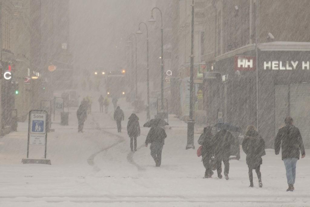 Folk på vandring i snøføyka på Karl Johans gate torsdag morgen.