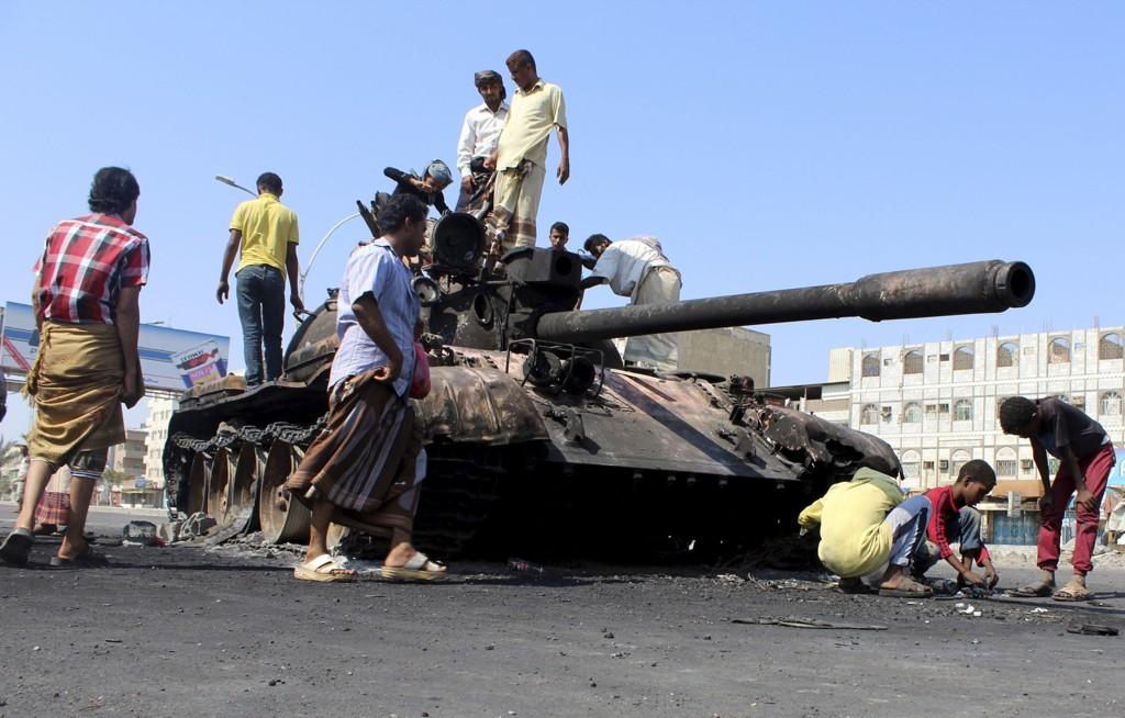 UTBRENT: En koalisjon av flere land står bak offensiven mot Houthi-militsen. Her har folk samlet seg ved en utbrent stridsvogn i den jemenittiske havnebyen Aden mandag.