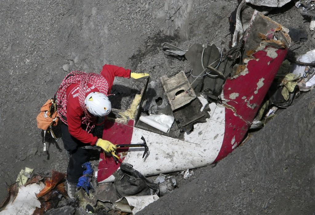 En fransk redningsarbeider studerer deler av Germanwings-flyet.