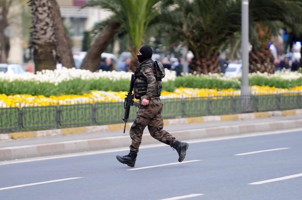 BLE ANGREPET: En tjenestemann fra politiets spesialstyrke løper for å innta sin posisjon utenfor politihovedkvarteret i Istanbul onsdag.