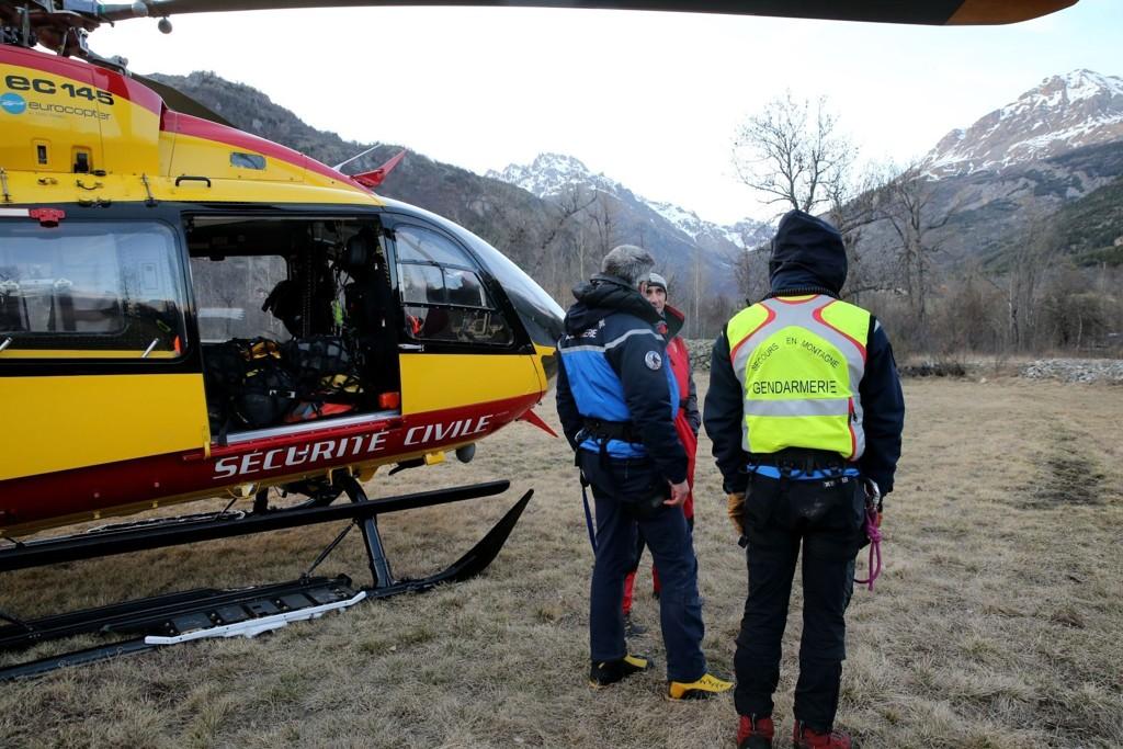 TRE OMKOM: Politi og redningsmannskap står ved et helikopter i Vallouise onsdag etter søket etter turistene som ble tatt av et stort snøskred i fjellområdet Massif des Ecrins.