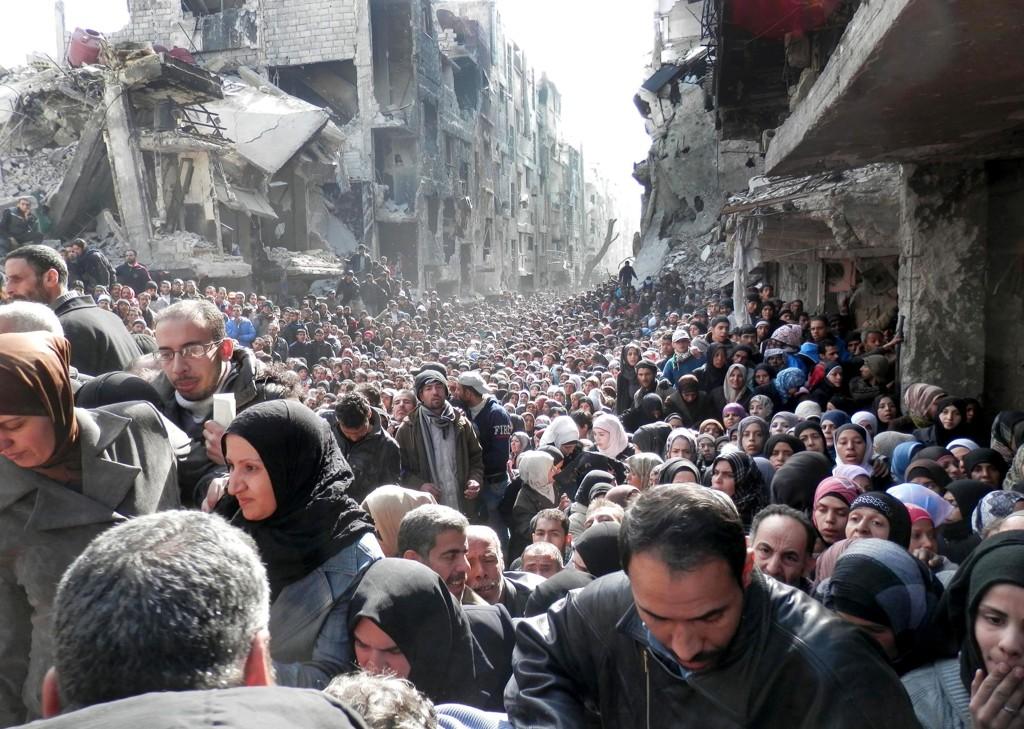 FRA VONDT TIL VERRE: På dette bildet tatt 31. januar 2014 stiller flyktninger seg i kø for nødhjelpsrasjoner i Yarmouk-leiren. Nå fortviler FN og hjelpeorganisjoner fordi de ikke får adgang til leiren.