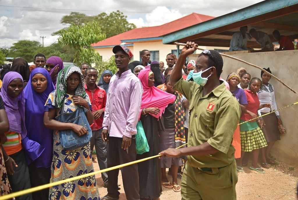VISTE FRAM LIK: En sikkerhetsvakt forsøker å holde folk tilbake som strømmer på for å se likene av mistenkte terrorister etter skolemassakren i Garissa.