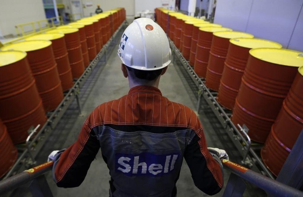 Illustrasjonsfoto: En ansatt i Royal Dutch Shell står foran en rekke oljetønner på selskapets fabrikk i Torzhok i Russland.