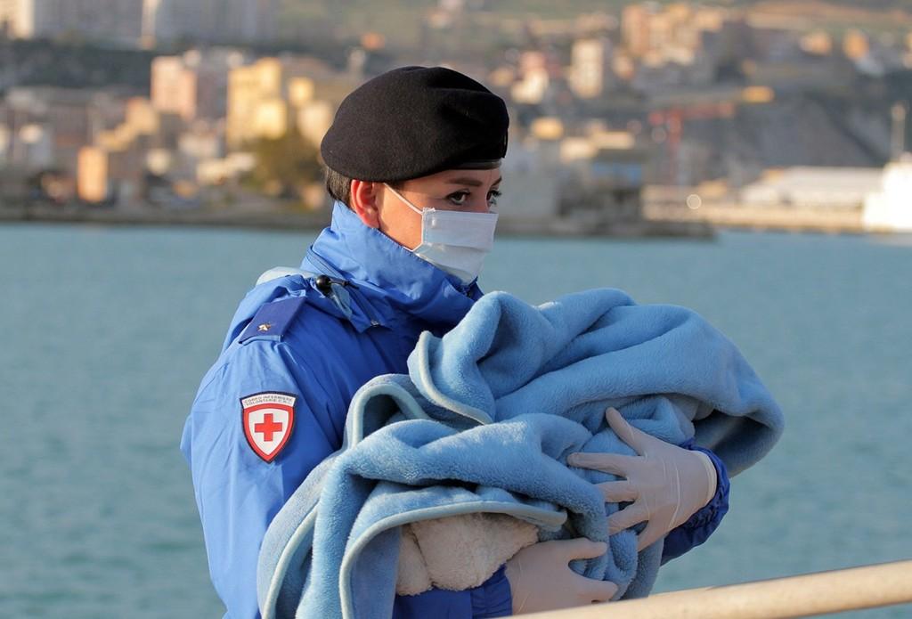 RØDE KORS: En baby bæres i land etter å ha blitt reddet i Middelhavet. Fremdeles skal 400 være savnet etter at båten de var i kantret.