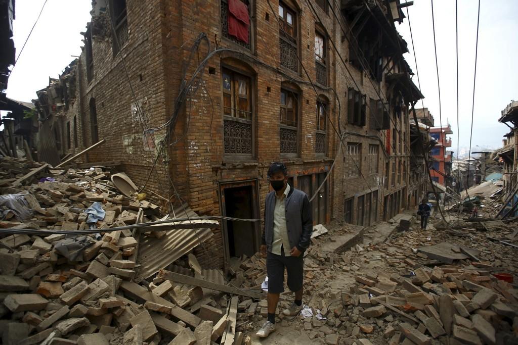 En mann går forbi ruinene av ødelagte hus etter jordskjelvkatastrofen i Nepal.