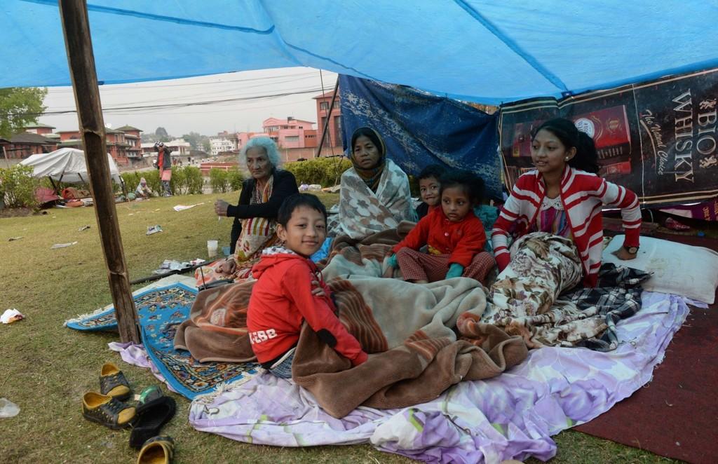 SOVER UTE: En familie har gjort dette til et midlertidig hjem i Kathmandu. Internasjonale hjelpeorganisasjoner jobber nå med å skaffe hjelp til de som ble rammet av jordskjelvet i Nepal lørdag.