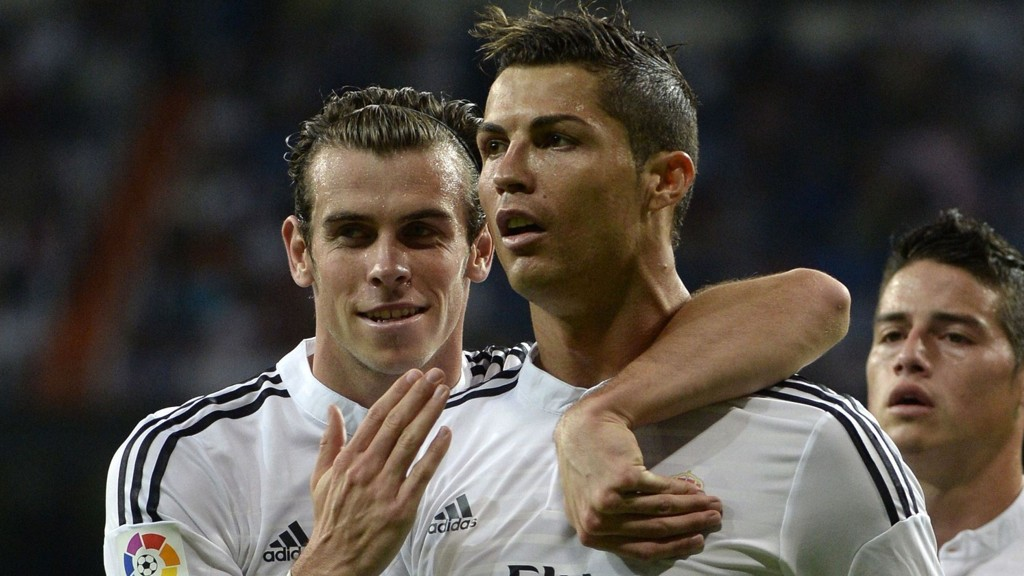 Real Madrid's Portuguese forward Cristiano Ronaldo (C) celebrates with Real Madrid's Welsh forward Gareth Bale after scoring during the Spanish league football match Real Madrid CF vs Elche CF at the Santiago Bernabeu stadium in Madrid on September 23, 2014. AFP PHOTO / GERARD JULIEN