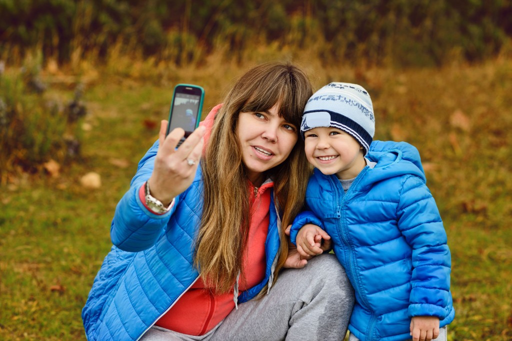mother and her son outdoors making selfie