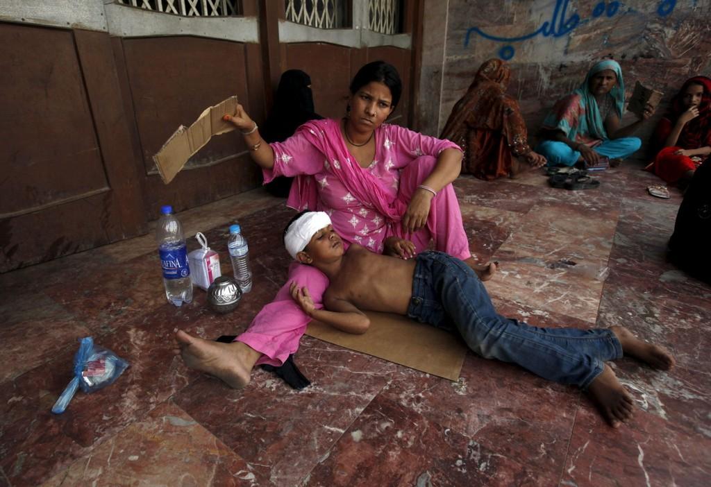 En kvinne bruker et stykke papp som vifte over sønnen på venterommet til en klinikk i Karachi sør i Pakistan tirsdag.