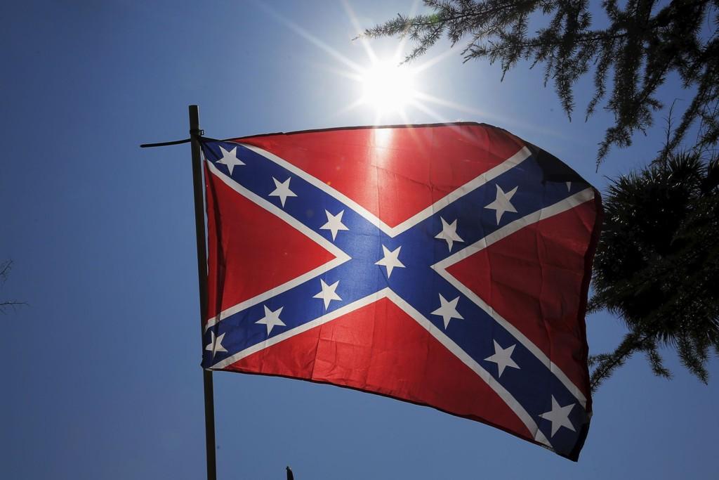 OMSTRIDT: Et sørstatsflagg er fotografert under en demonstrasjon foran South Carolinas delstatsforsamling tirsdag. Fra nå av skal det ikke lenger pryde delstatens offentlige myndigheter