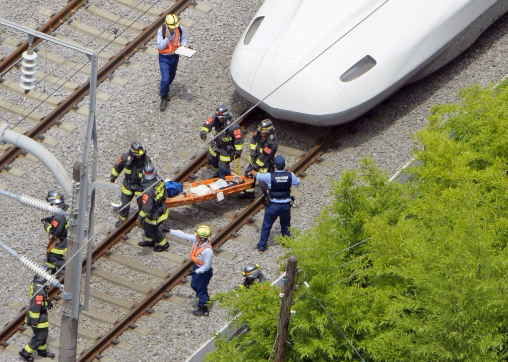 Redningsmannskaper henter ut en passasjer fra det hurtigtoget som ble stanset av en brann tirsdag