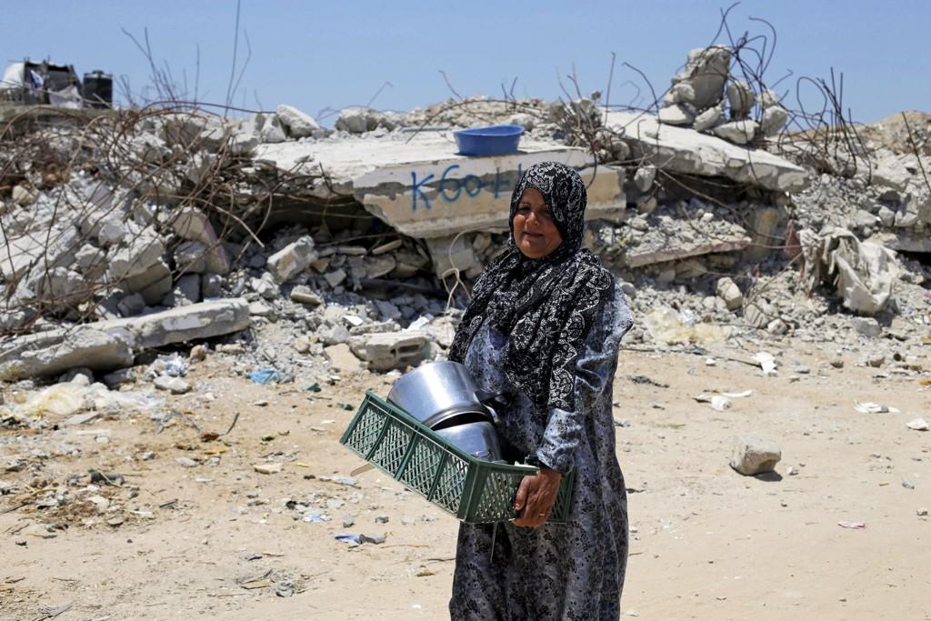 En palestinsk kvinne går forbi ruinene av huset hun bodde i. Huset ble ødelagt under et av Israels mange luftangrep i fjor sommer. Ett år senere er så godt som ingen av de 10.000 ødelagte boligene bygge opp. Foto: Ibraheem Abu Mustafa, REUTERS/NTB scanpix.
