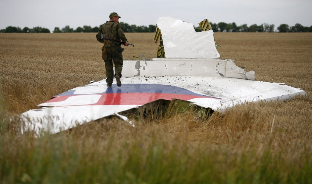 En prorussisk opprører står på en vrakdel fra Malaysia Airlines-flyet som ble skut ned over Øst-Ukraina. Hvem som har ansvaret er ennå ikke klart. Den endelige rapporten kommer i oktober.