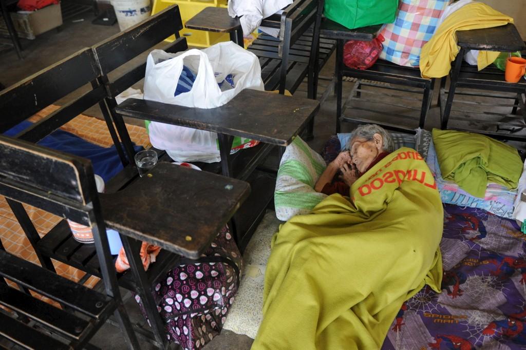 Kraftig monsunregn de siste dagene har ført til at rundt 3.000 mennesker er blitt evakuert, opplyser filippinske myndigheter søndag. På bildet er en kvinne fotografert på en skole etter å ha blitt evakuert tidligere denne måneden.