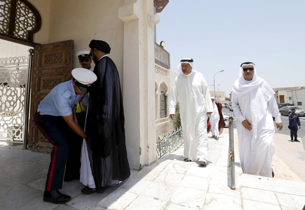 De fire mennene som er pågrepet, er kuwaitiske statsborgere og skal i avhør ha innrømmet å ha mottatt militærtrening. Bildet viser en politimann som kroppsvisiterer en mann ved inngangen til en moske ved byen Manama i juli.