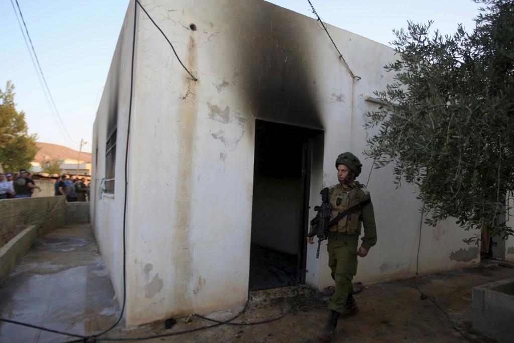 MORDBRANN: Meir Ettinger er ikke direkte anklaget for å være innblandet i fredagens mordbrann. På bildet går en israelsk soldat vakt ved huset der en 18 måneder gammel baby døde. Foreldrene og hans fire år gamle bror ligger alvorlig skadd på sykehus.