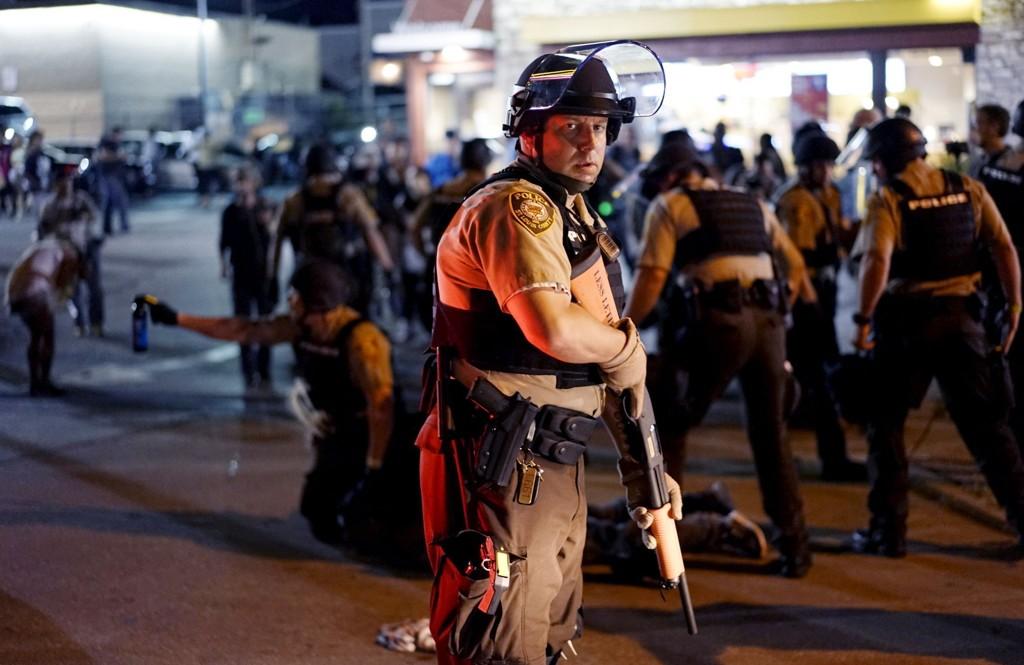 En politimann under demonstrasjonene i Ferguson mandag. I bakgrunnen blir en demonstrant pågrepet.