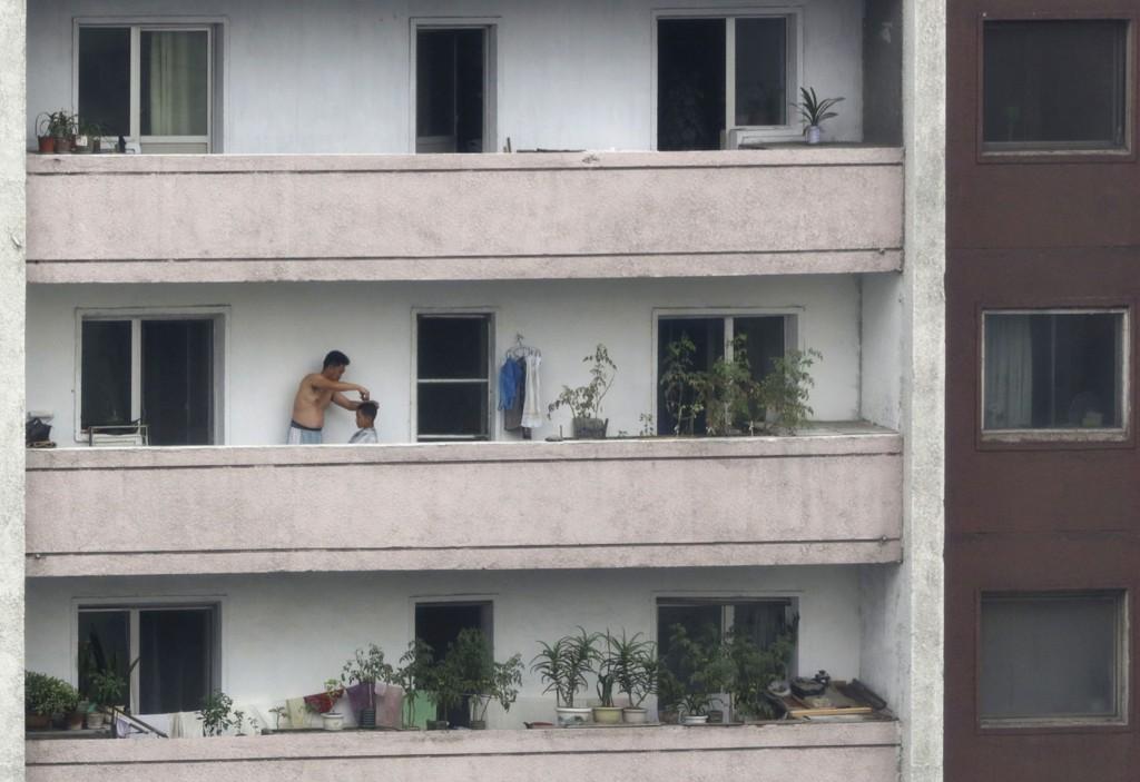 En mann klipper en gutt på en balkong i Pyongyang, 15. august 2015.