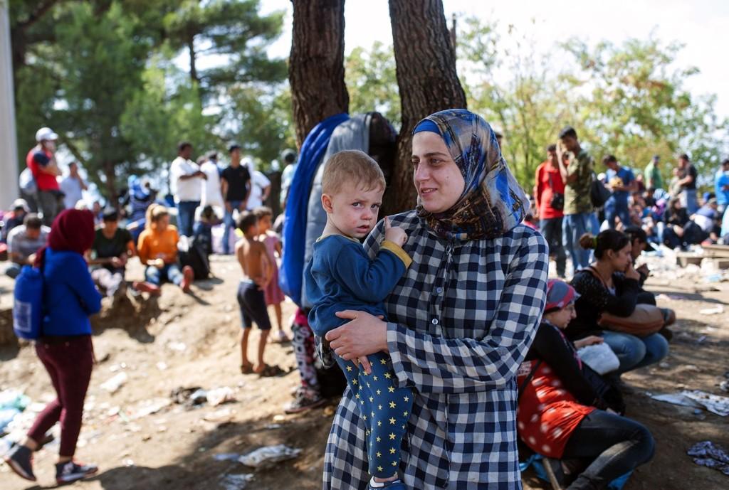 En kvinne og et lite barn venter på å krysse grensen mellom Makedonia og Hellas i byen Gevgelija.