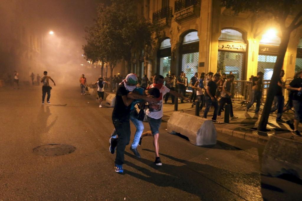 Demonstranter løper under en protest mot korrupsjon og søppelproblemer i nærheten av regjeringsbygningene i Beirut lørdag kveld.