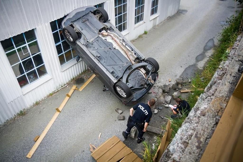 HØYT FALL: Her endte turen for bilen som begynte å trille og trillet inn i en hage, gjennom et gjerde, før den falt cirka fire meter ned på en liten vei. Foto: Yngve Garen Svardal/Avisa Nordhordland