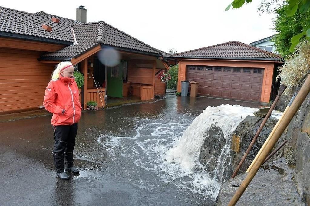 Ingebjørg Magnussen foran huset som ble skadet av vannmassene.