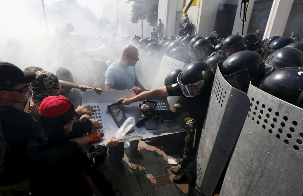 Demonstranter som er imot å gi de prorussiske områdene i Øst-Ukraina større selvstyre, slåss mot politiet utenfor nasjonalforsamlingen i Kiev.