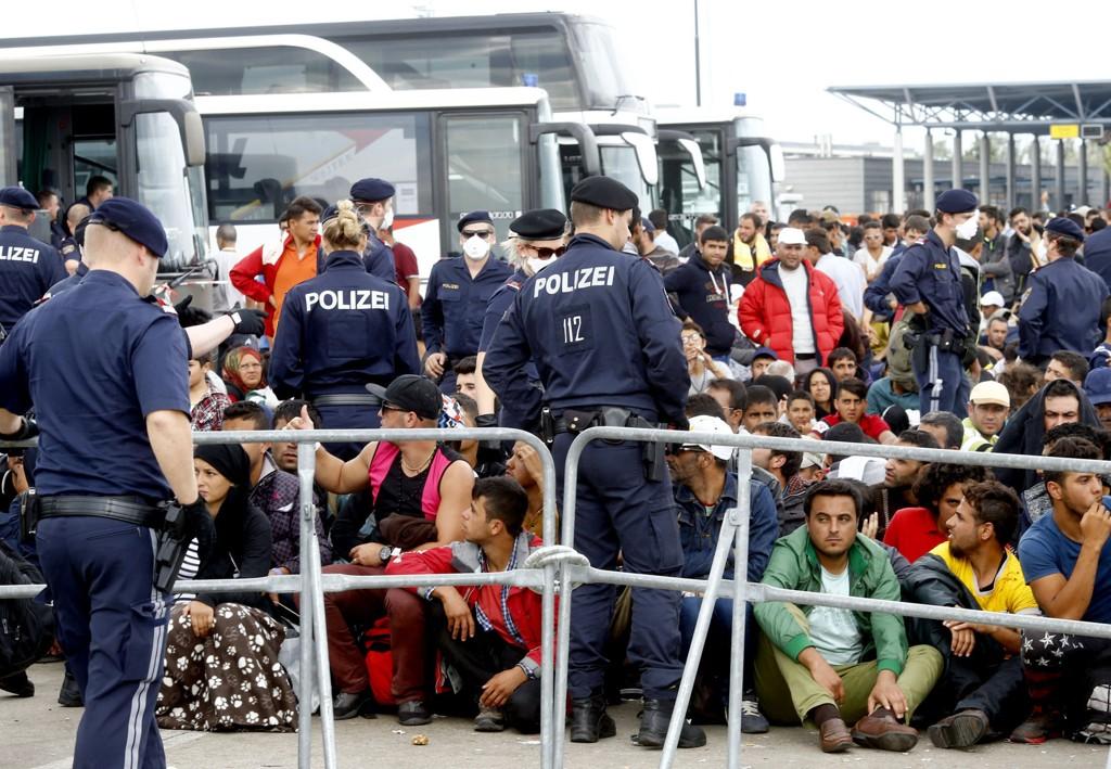 STENGER GRENSENE: Østerrike og Slovakia følger Tyskland og gjeninnfører grensekontroll mellom Schengen-land. Her venter migranter ved Nickelsdorf i Østerike mandag. Tusenvis kom inn i landet fra Ungarn mandag.