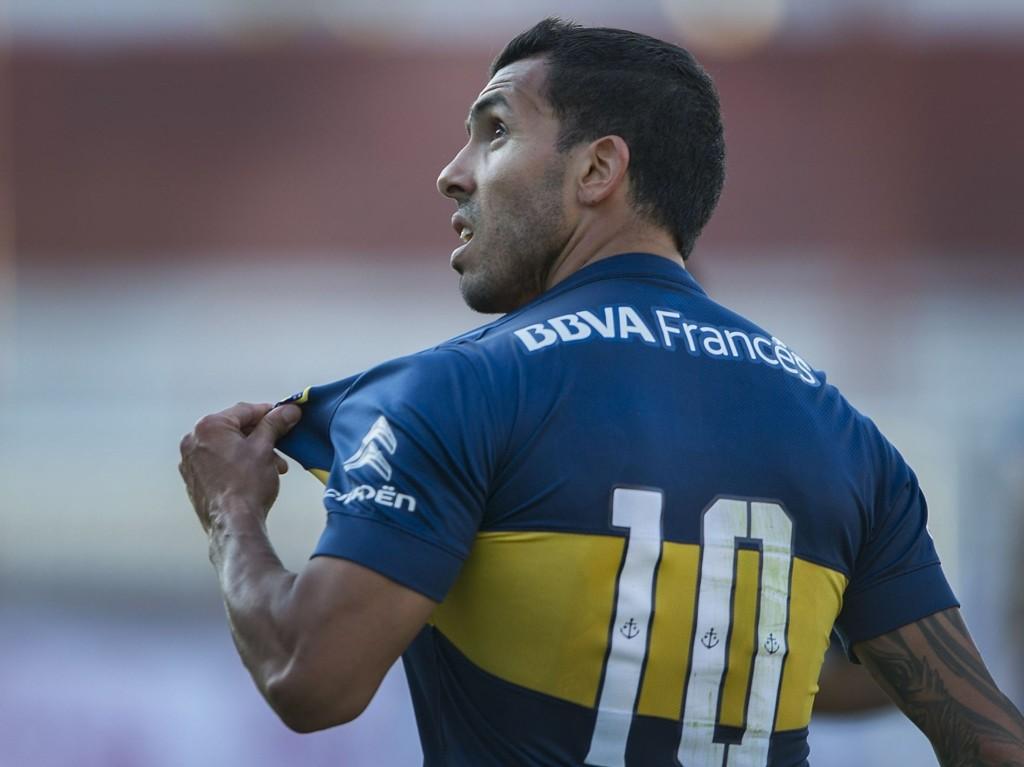 MÅL OG KONTROVERSER: Carlos Tévez feirer et av sine to mål mot Argentinos Juniors på Diego Armando Maradona stadion lørdag. Mest oppmerksomhet fikk han imidlertid for en annen hendelse i oppgjøret.
