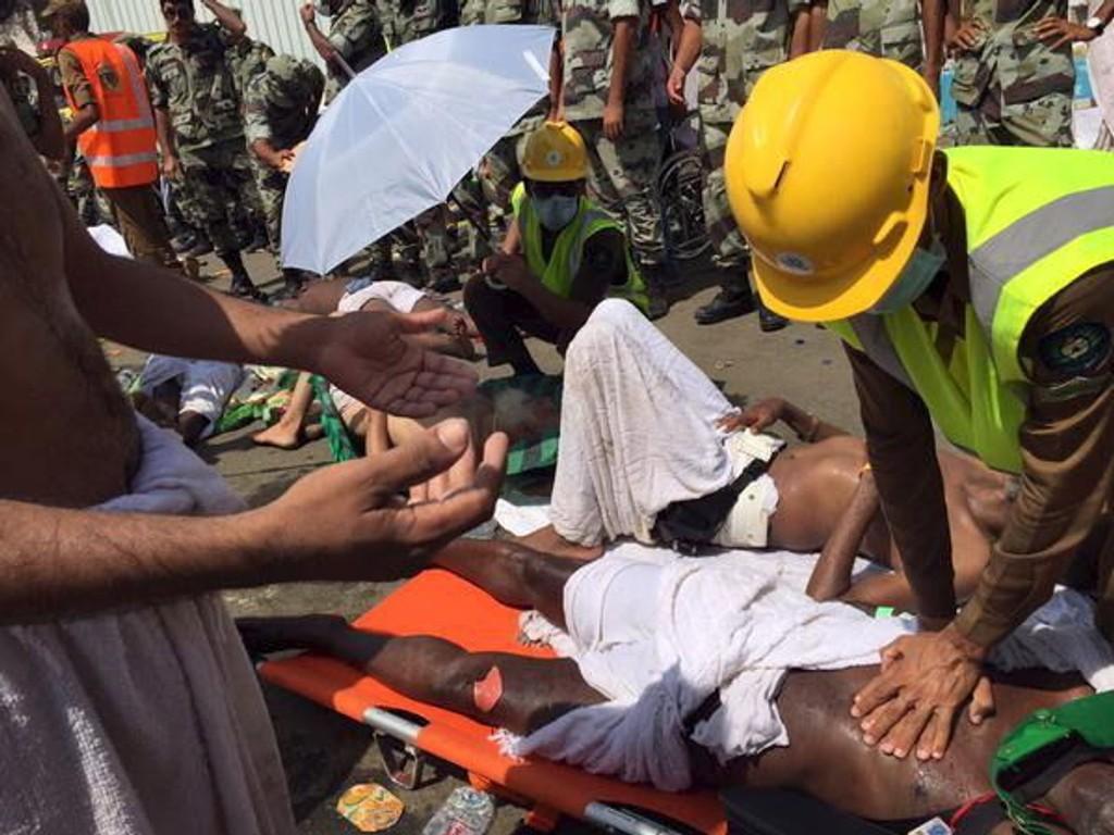 Medlemmer av det saudiarabiske sivilforsvaret gir førstehjelp til pilegrimer som ble skadd da det oppsto trengsel og panikk i folkemengden under pilegrimsvandringen hajj utenfor Mekka torsdag.